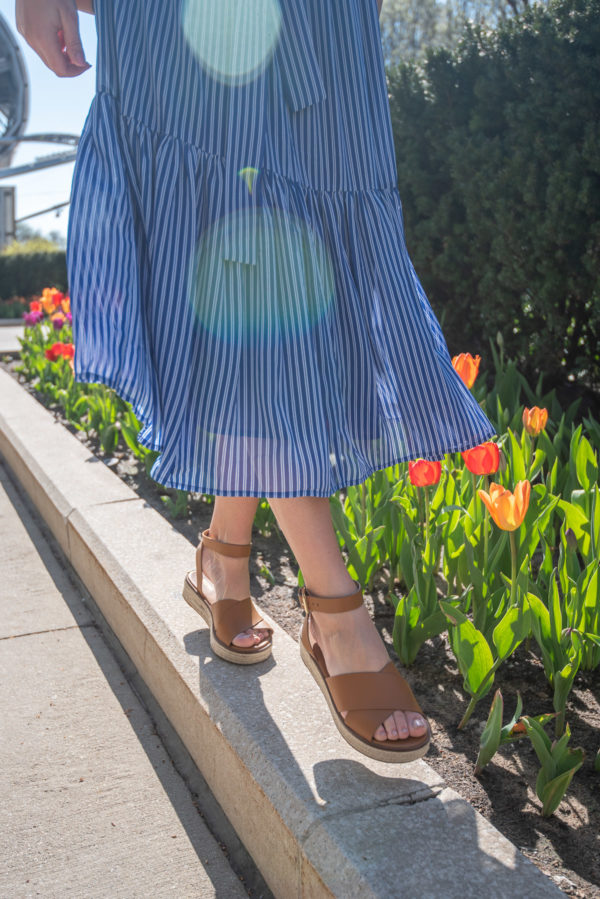 Fashion blogger wearing Michael Kors leather sandals in front of tulips with a striped midi dress.
