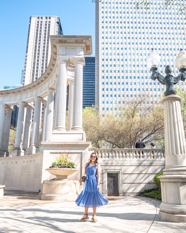Chicago lifestyle blogger Bows & Sequins twirling in a blue dress in Millennium Park.
