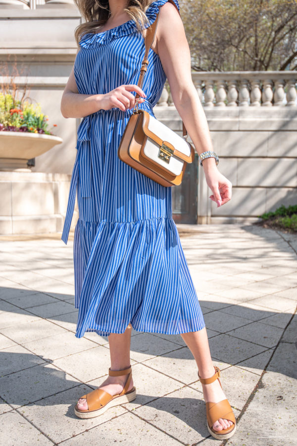 Chicago stylist wearing a blue and white dress with the Michael Kors Sloan Editor Large Canvas Shoulder Bag.