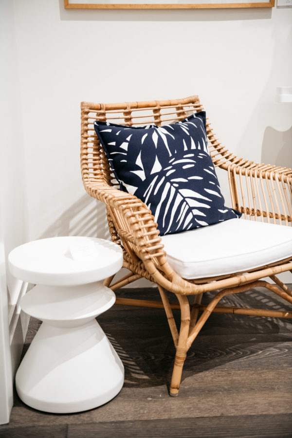 Serena & Lily Rattan Chair with blue and white printed pillows.
