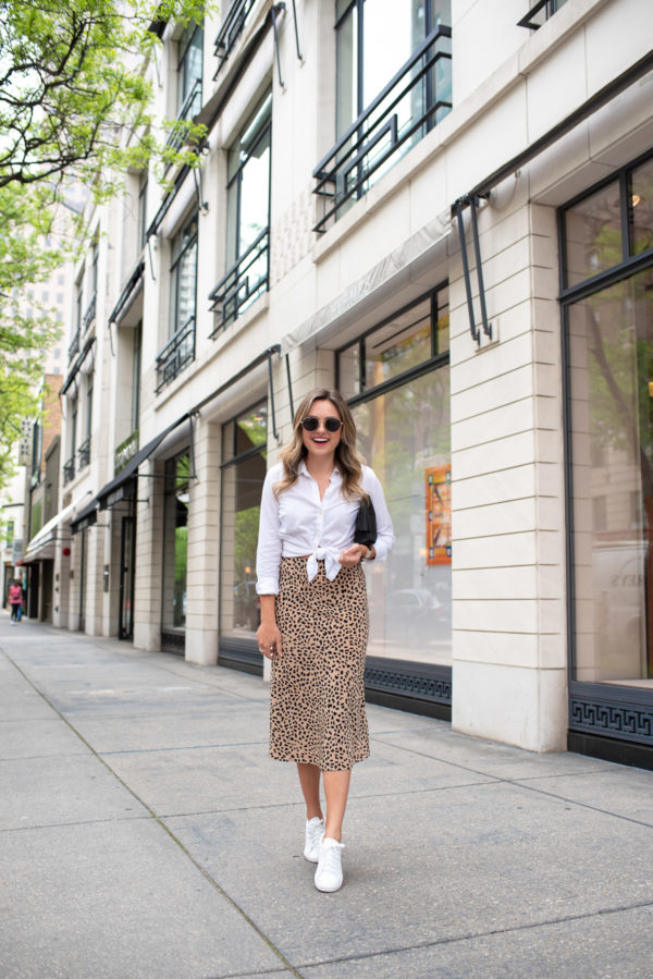 Chicago fashion and lifestyle blogger Jessica Sturdy of Bows & Sequins styling an animal print midi skirt with white leather sneakers on Oak Street in the Gold Coast.