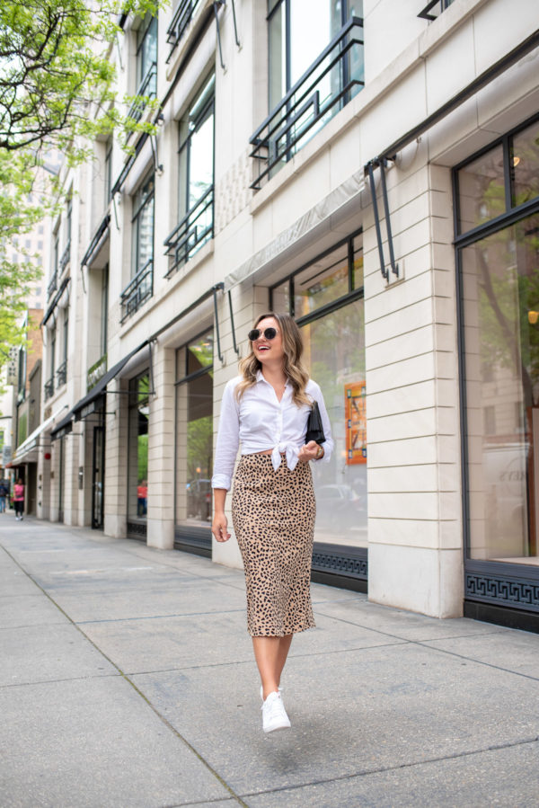Chicago lifestyle blogger Jessica Rose Sturdy styling a leopard print midi skirt with a white collared shirt and tennis shoes.