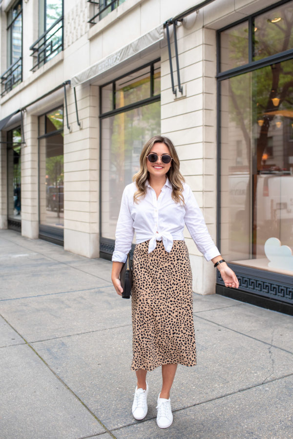 Fashion and lifestyle influencer Jessica Rose Sturdy wearing a cropped white shirt with a leopard skirt and white tennis shoes for work.
