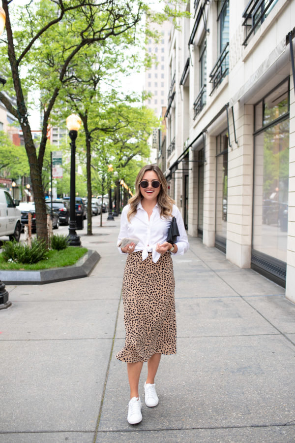 Fashion and style blogger Jessica Rose Sturdy styling a leopard midi skirt with a white oxford shirt and classic white tennis shoes.