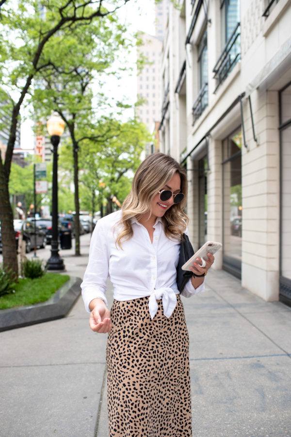 Chicago style blogger Bows & Sequins wearing a Vineyard Vines shirt with an animal print skirt.