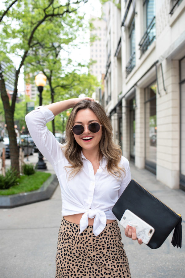 Chicago wellness blogger Bows & Sequins wearing a white collared skirt with a leopard skirt.