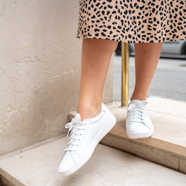 Chicago fashion influencer Bows & Sequins wearing all white sneakers from Keds with an animal print skirt.