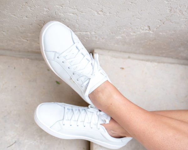 Bows & Sequins wearing the all white leather Keds Ace sneakers.