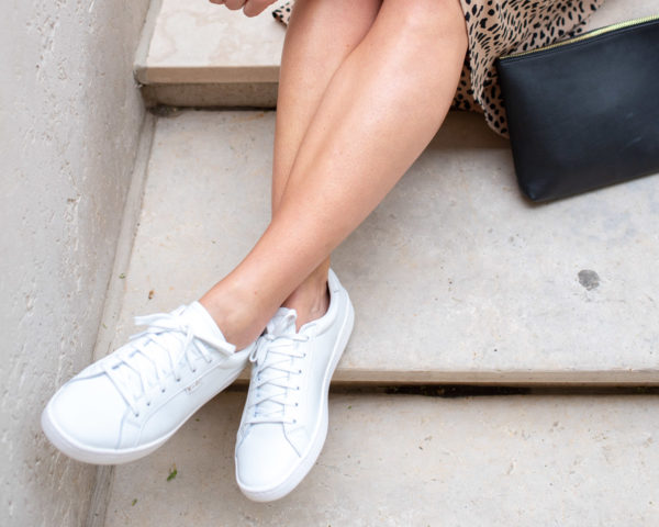 Chicago blogger Bows & Sequins wearing the Keds Ace sneakers in all white leather with a cheetah midi skirt.