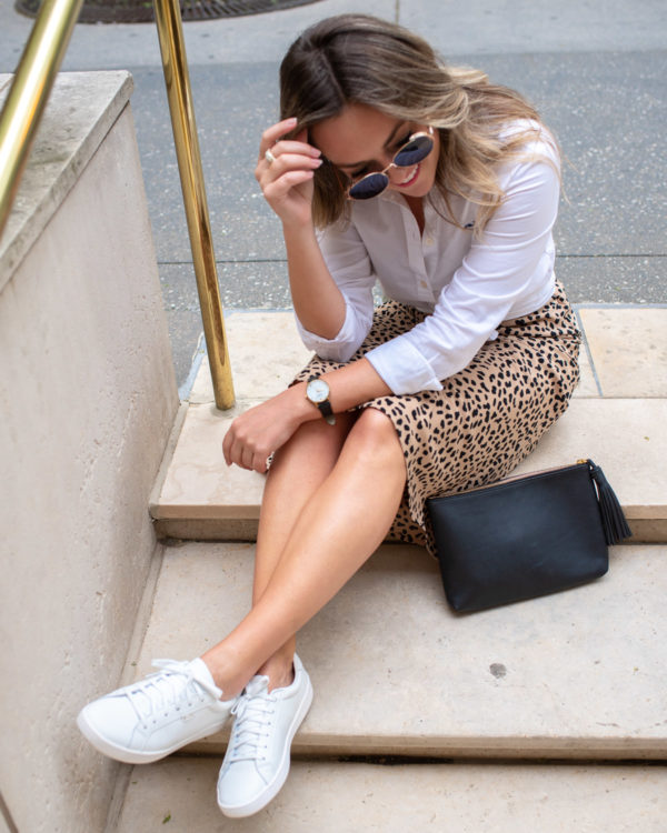 Fashion blogger styling an outfit with Keds sneakers and a leopard skirt.