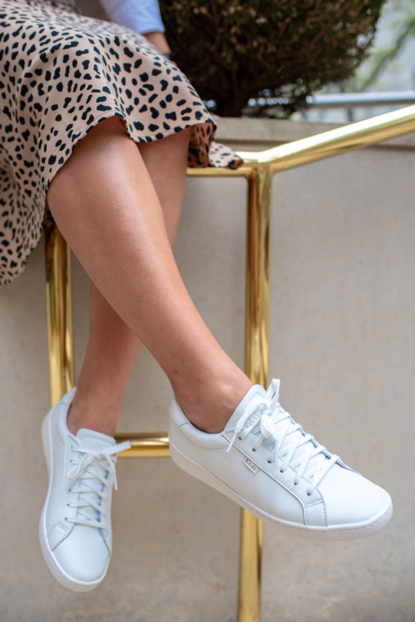 Fashion blogger Bows & Sequins styling the Keds White Leather Ace Sneakers with a leopard skirt.