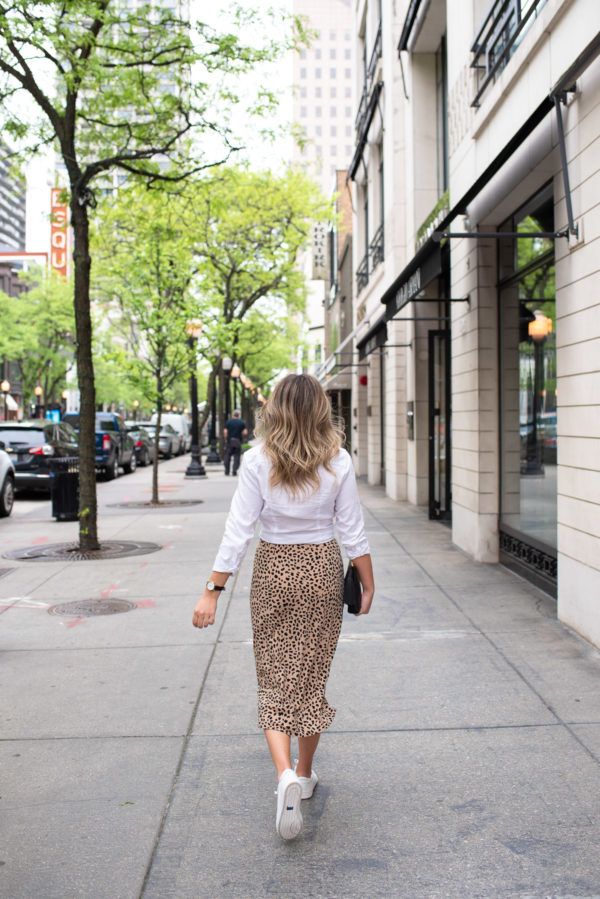 Fashion and lifestyle influencer Bows & Sequins styling a leopard midi skirt with a white button front shirt and sneakers.