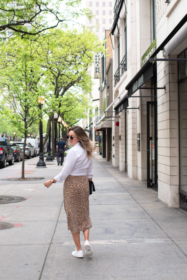 Chicago lifestyle blogger Jessica Sturdy of Bows & Sequins styling a leopard skirt with white sneakers for a cute workwear look.