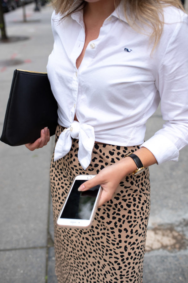 Fashion and outfit blogger Bows & Sequins styling a tied-up Vineyard Vines collared shirt with a leopard pencil skirt.