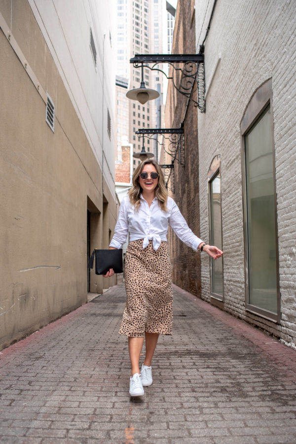 Top Chicago blogger Jessica Sturdy of Bows & Sequins styling a leopard midi skirt with white sneakers.