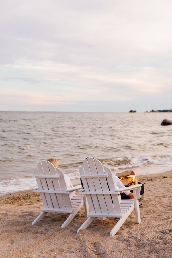 White Adirondack Chairs and a Beach Bonfire at Wee Burn Beach Club in Connecticut at Sunset
