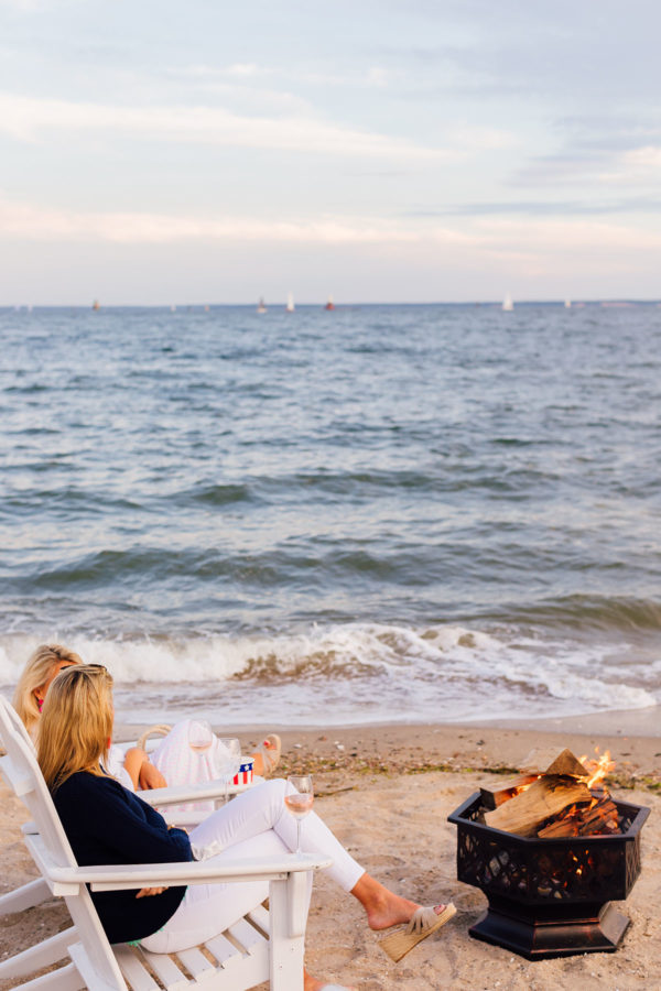 Two girls sitting in white adirondack chairs by a sunset beach bonfire at Wee Burn Beach Club in Connecticut