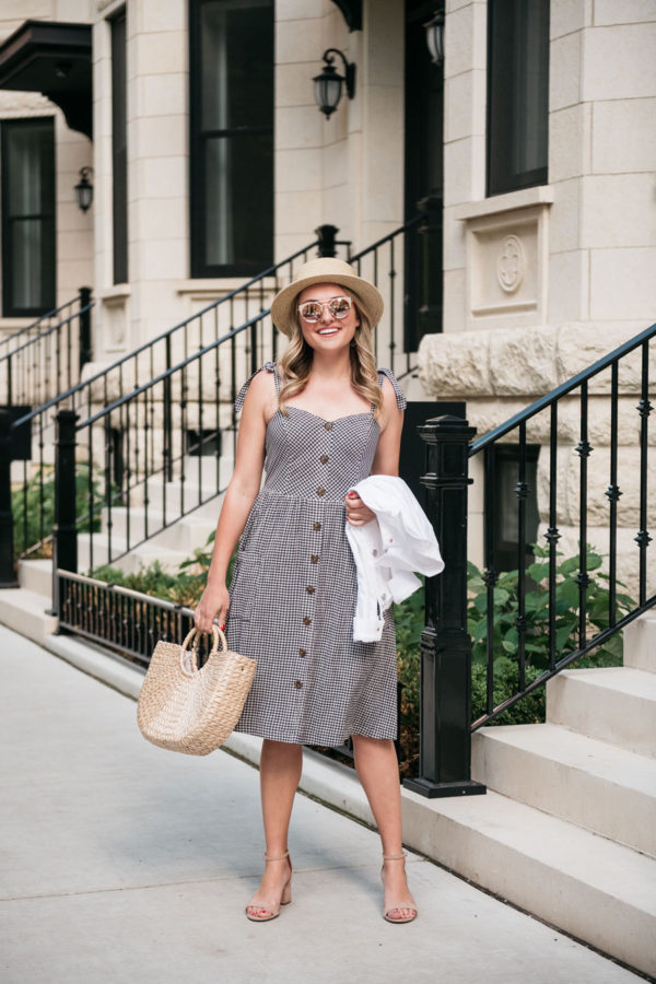 Chicago blogger wearing a gingham dress with a straw hat.