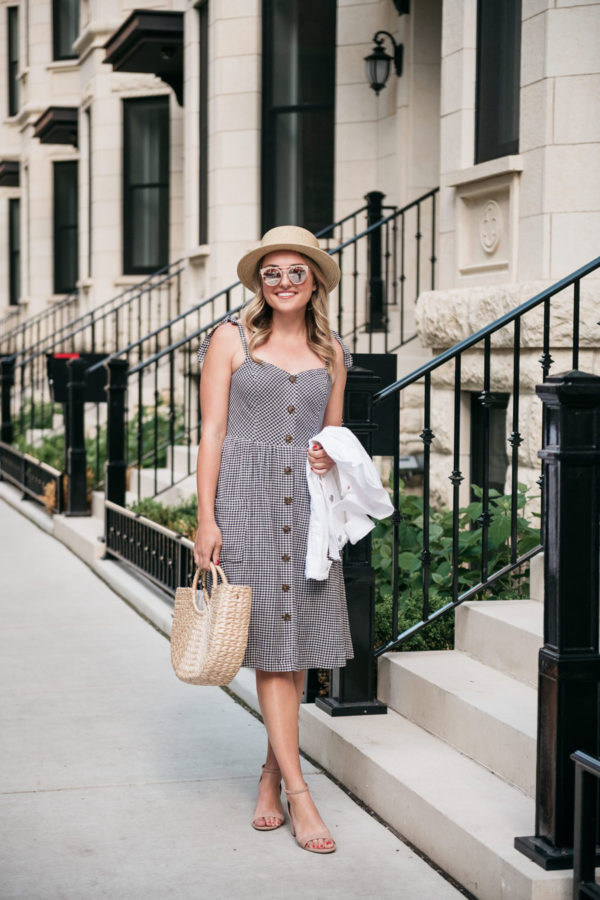 Chicago lifestyle blogger Bows & Sequins wearing a gingham dress with a hat and a straw tote.