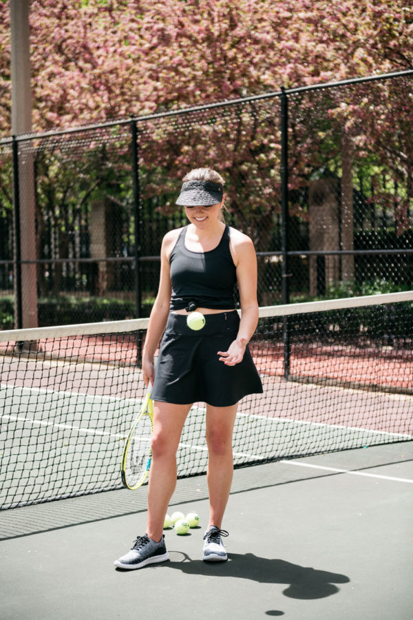 Chicago blogger Bows & Sequins playing tennis in black skort and visor.