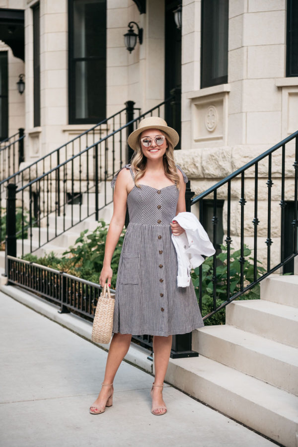 Chicago fashion blogger wearing a gingham dress with a white denim jacket and blush pink heels.