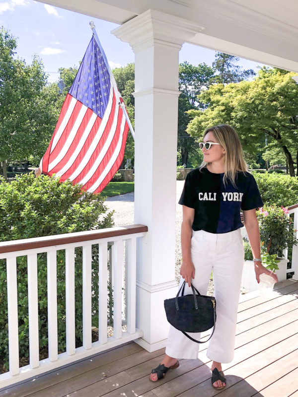 Lifestyle blogger Jessica Sturdy of Bows & Sequins wearing a Cynthia Rowley Cali York tee shirt with Vineyard Vines cropped wide leg white chino pants, a black Clare V straw tote, and black slides.