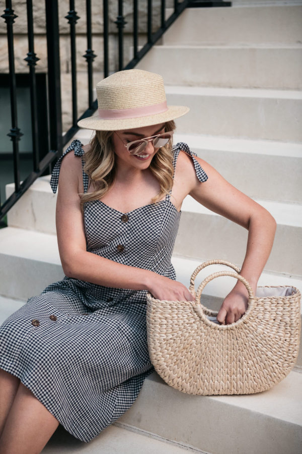 Lifestyle blogger wearing a gingham dress with a packable straw hat with a blush pink band.