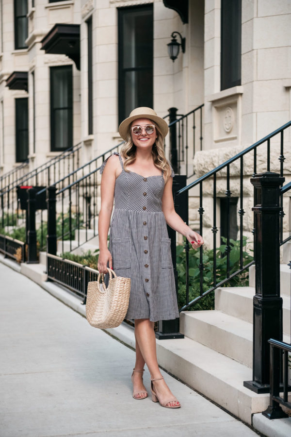 Chicago lifestyle Instagrammer Bows & Sequins styling a gingham dress with a straw tote.