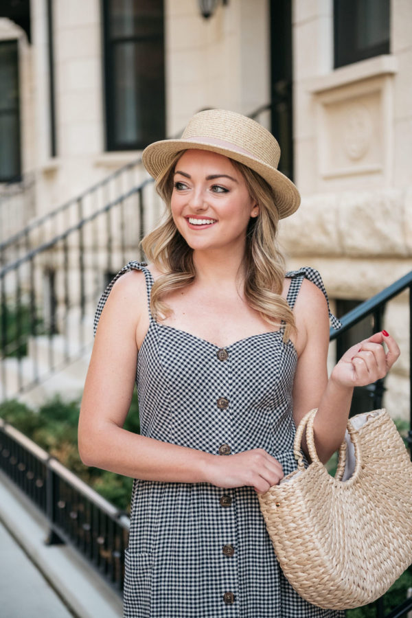 Beauty blogger Bows & Sequins wearing a boater hat with a gingham dress.