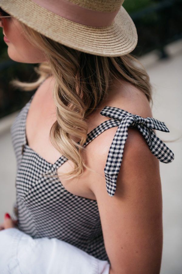 Preppy lifestyle blogger Jessica Sturdy of Bows & Sequins wearing a gingham dress with bow-tied straps.