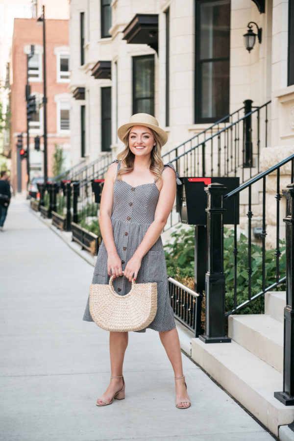 Chicago lifestyle blogger wearing a gingham dress with a structured straw tote.