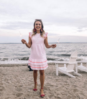 Preppy fashion blogger Jessica Sturdy of Bows & Sequins wearing a Sail to Sable funfetti dress on the beach with sparklers at Wee Burn Beach Club in Rowayton, CT.