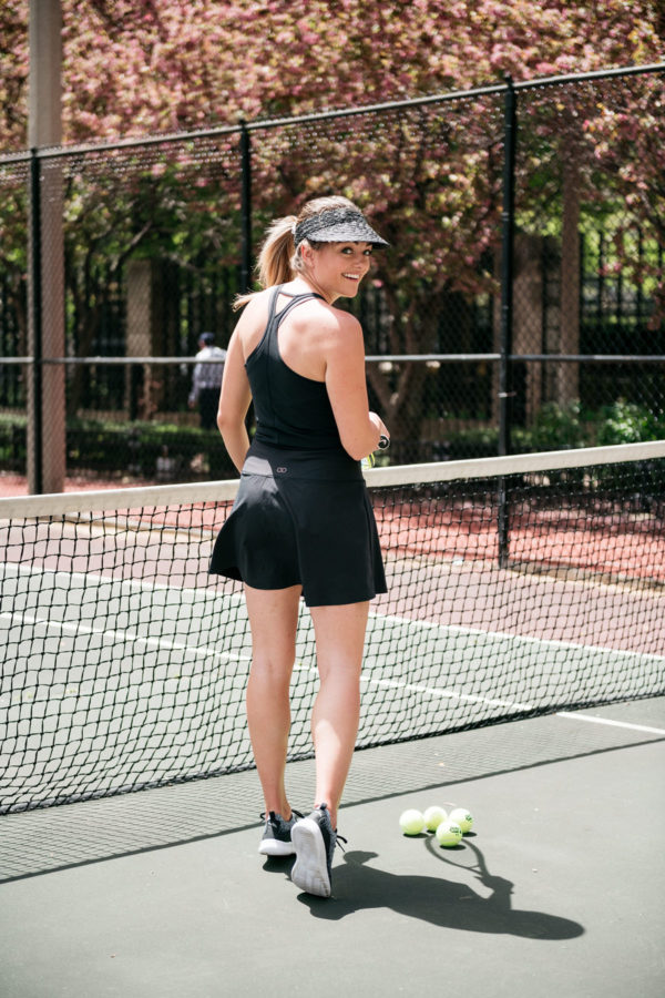 Chicago health and wellness blogger Jessica Sturdy of Bows & Sequins playing tennis in a black skort and visor near the lake in Streeterville.