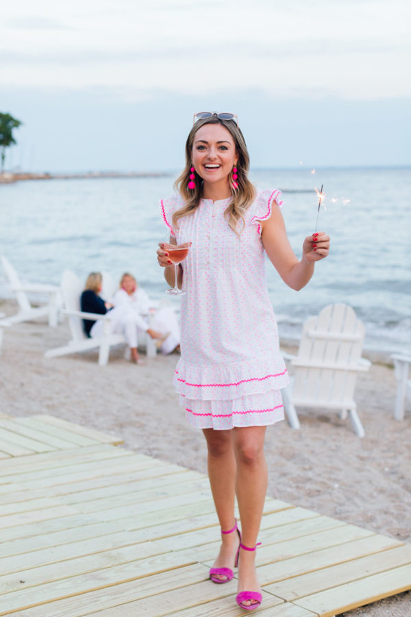 Fun lifestyle blogger Jessica Sturdy of Bows & Sequins wearing a Sail to Sable Dress with a glass of Whispering Angel rosé and a sparkler at Wee Burn Beach Club in Connecticut.