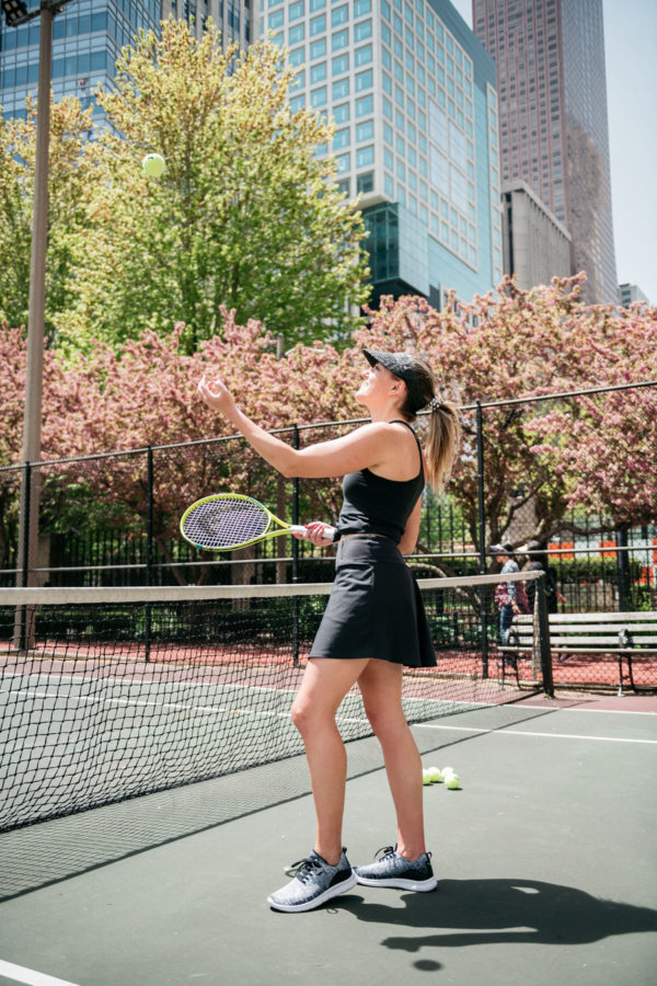 Chicago fitness blogger Jessica Sturdy of Bows & Sequins playing tennis in an all black outfit with a skort and visor.