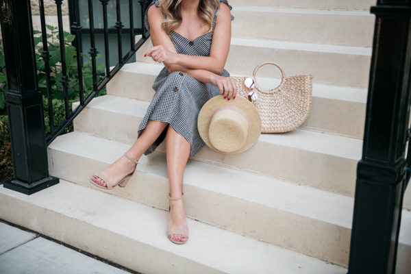 Chicago blogger styling a gingham sundress with a packable straw hat.