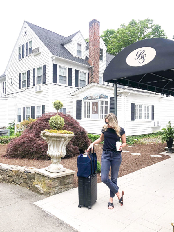 Travel blogger with an Away Bigger Carry-On suitcase outside of the Roger Sherman Inn in New Canaan, Connecticut