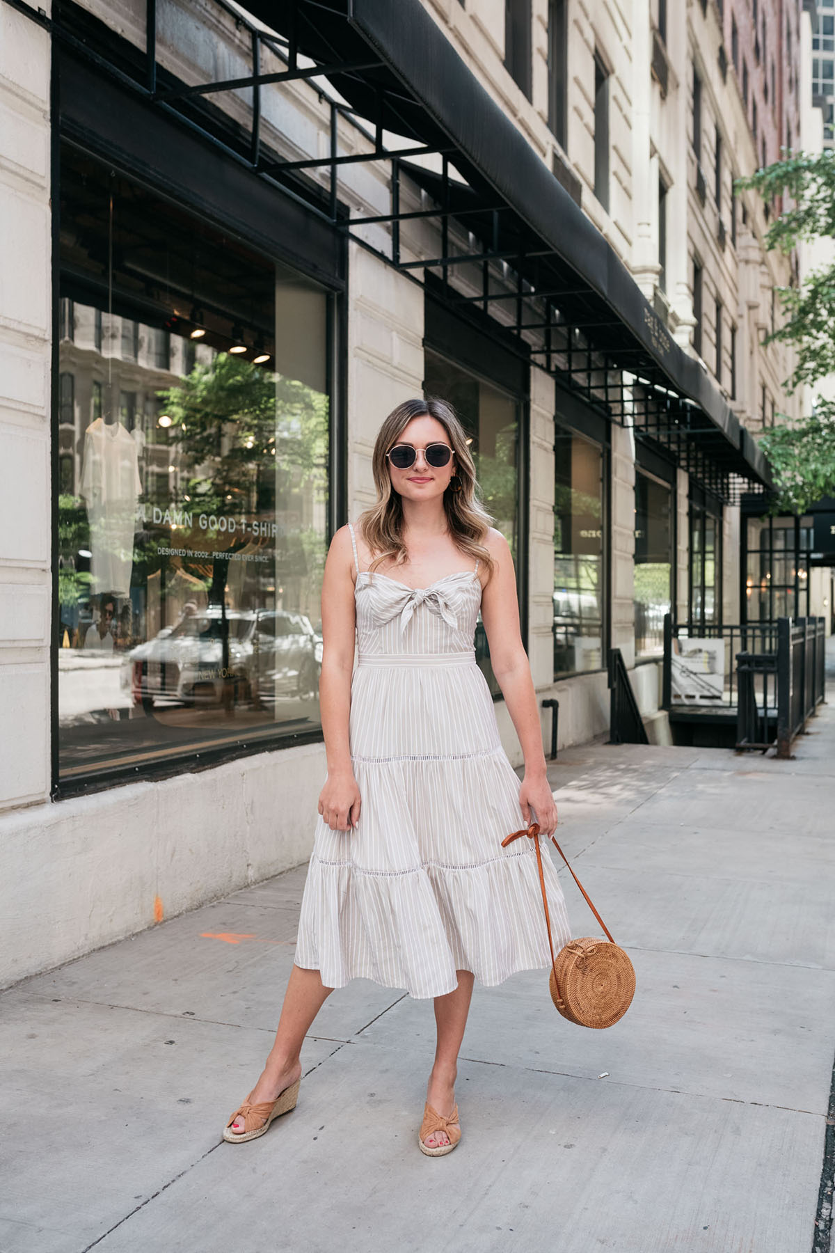 Bows & Sequins wearing a neutral striped midi dress with a round rattan handbag in Chicago.