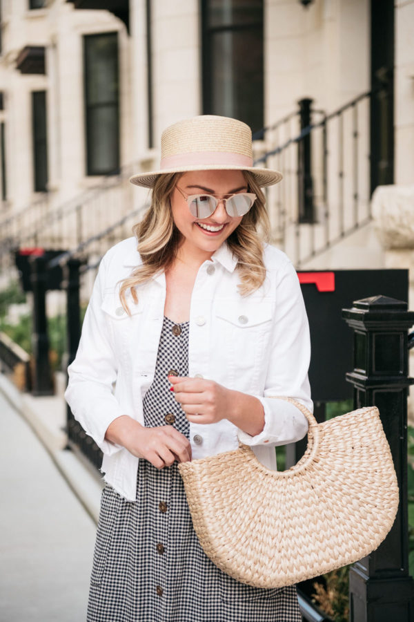 Bows & Sequins wearing a straw hat with a white denim jacket and structured straw tote.
