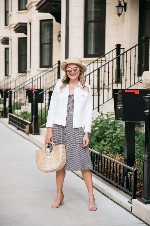 Chicago style blogger Bows & Sequins wearing a gingham dress with a white denim jacket and straw hat.