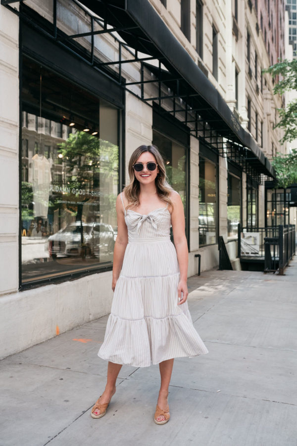 Chicago personal style blogger Jessica Sturdy of Bows & Sequins twirling in a neutral dress in front of rag & bone in the Gold Coast.