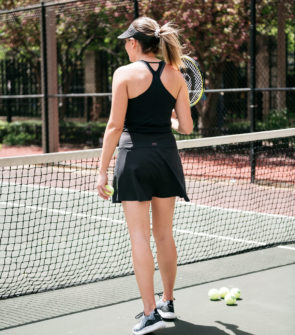 Chicago blogger Bows & Sequins styling a black visor and a tennis skort.