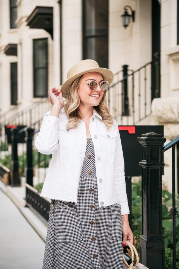 Chicago fashion blogger wearing a white denim jacket over a gingham dress.