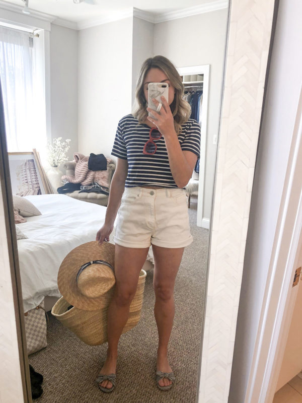 Chicago blogger wearing white high waisted jean shorts with a striped tee and straw tote for boating on Lake Michigan.
