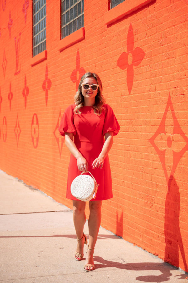 Chicago fashion and beauty blogger Jessica Sturdy of Bows & Sequins wearing a red dress with white accessories in front of the orange Louis Vuitton pop-up store.