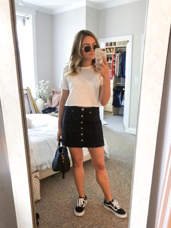 Fashion blogger wearing a black jean skirt and cropped tee with Vans to a baseball game.