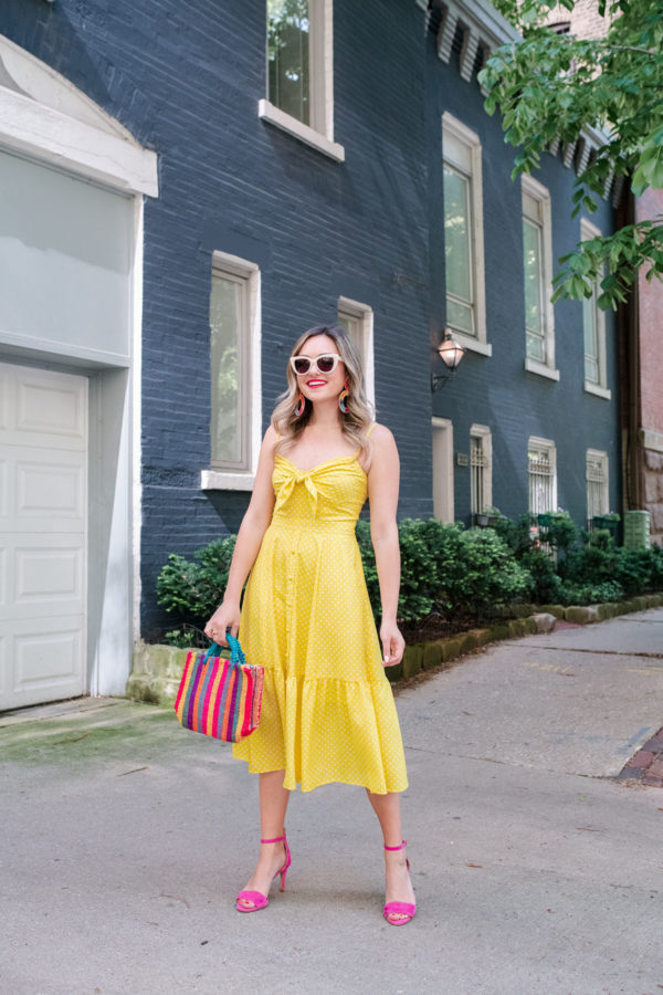 Chicago lifestyle blogger Jessica Sturdy wearing a yellow bow front midi dress with pink shoes and a colorful striped bag.