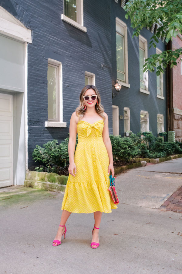 Fashion and beauty blogger Jessica Sturdy styling a yellow polka dot midi dress with pink heels.