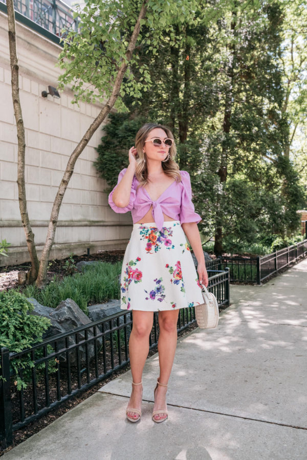 Feminine fashion blogger in Chicago styling a tie-front top with a floral skirt.