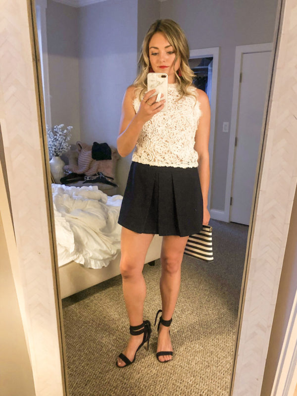 Fashion blogger Bows & Sequins wearing a white lace top with navy pleated shorts, a red lip, red BaubleBar statement earrings, a striped clutch, and navy lace-up heels for a fancy dinner on 4th of July weekend.